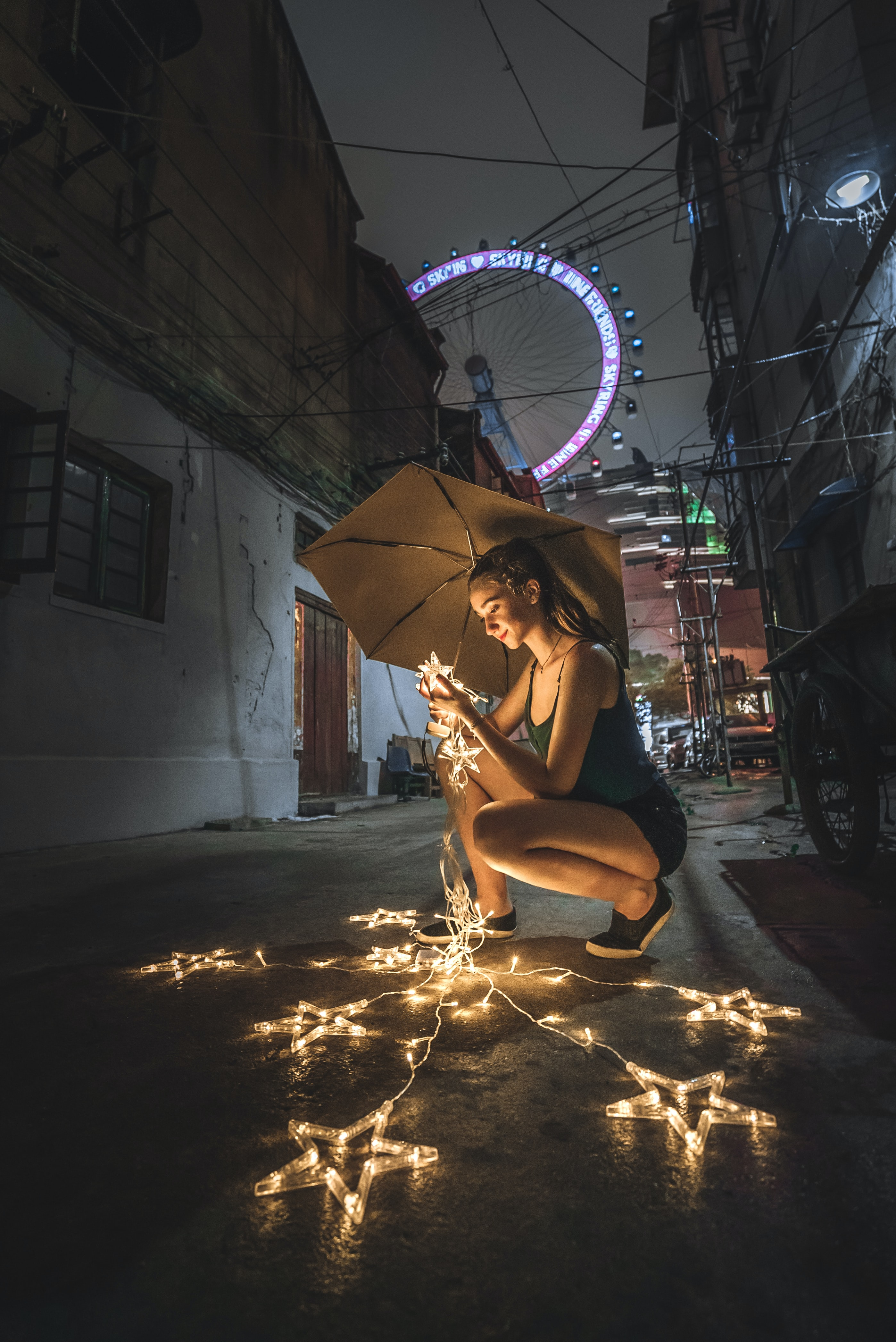 woman holding umbrella and string lights during nighttime