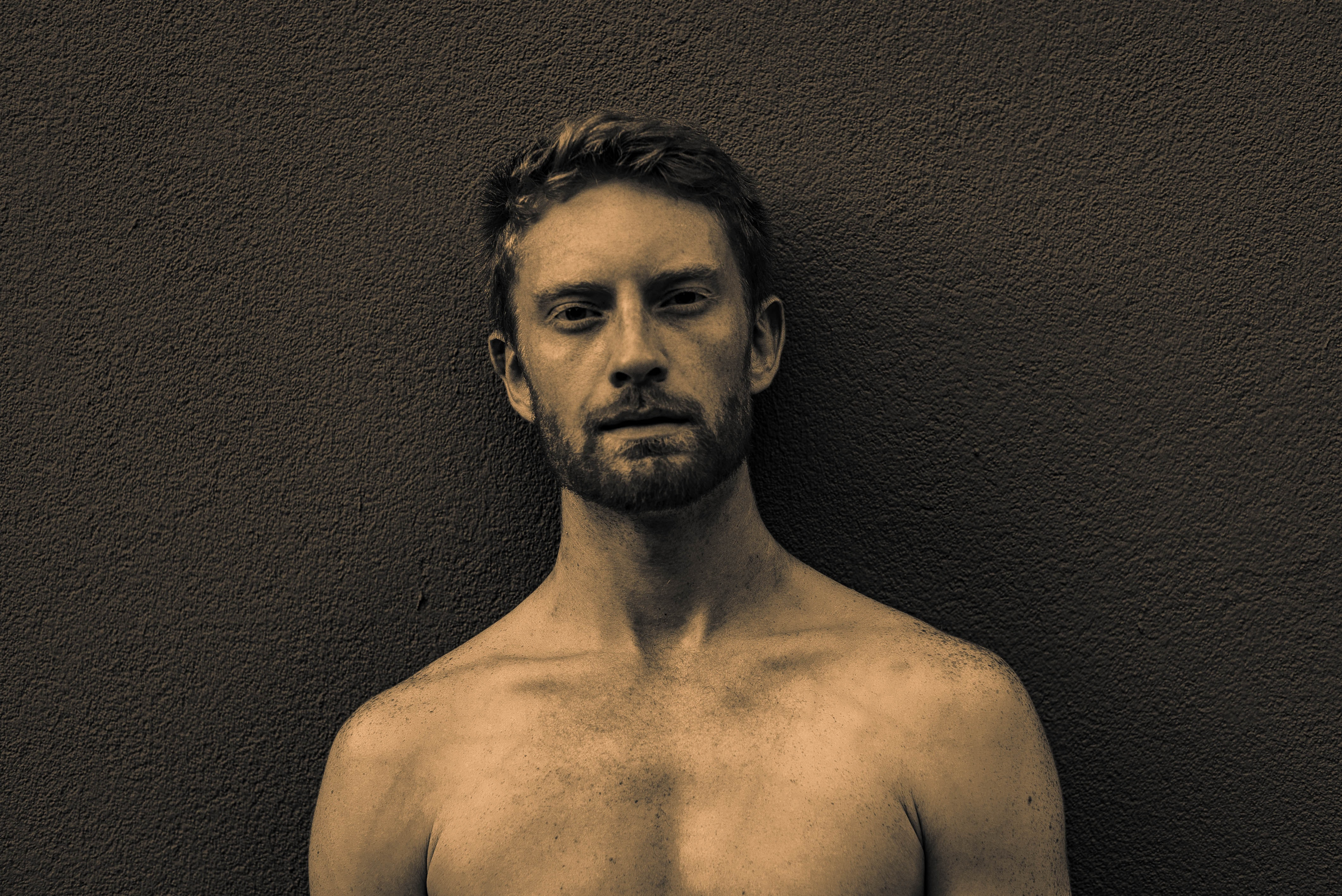 topless man standing against brown wall