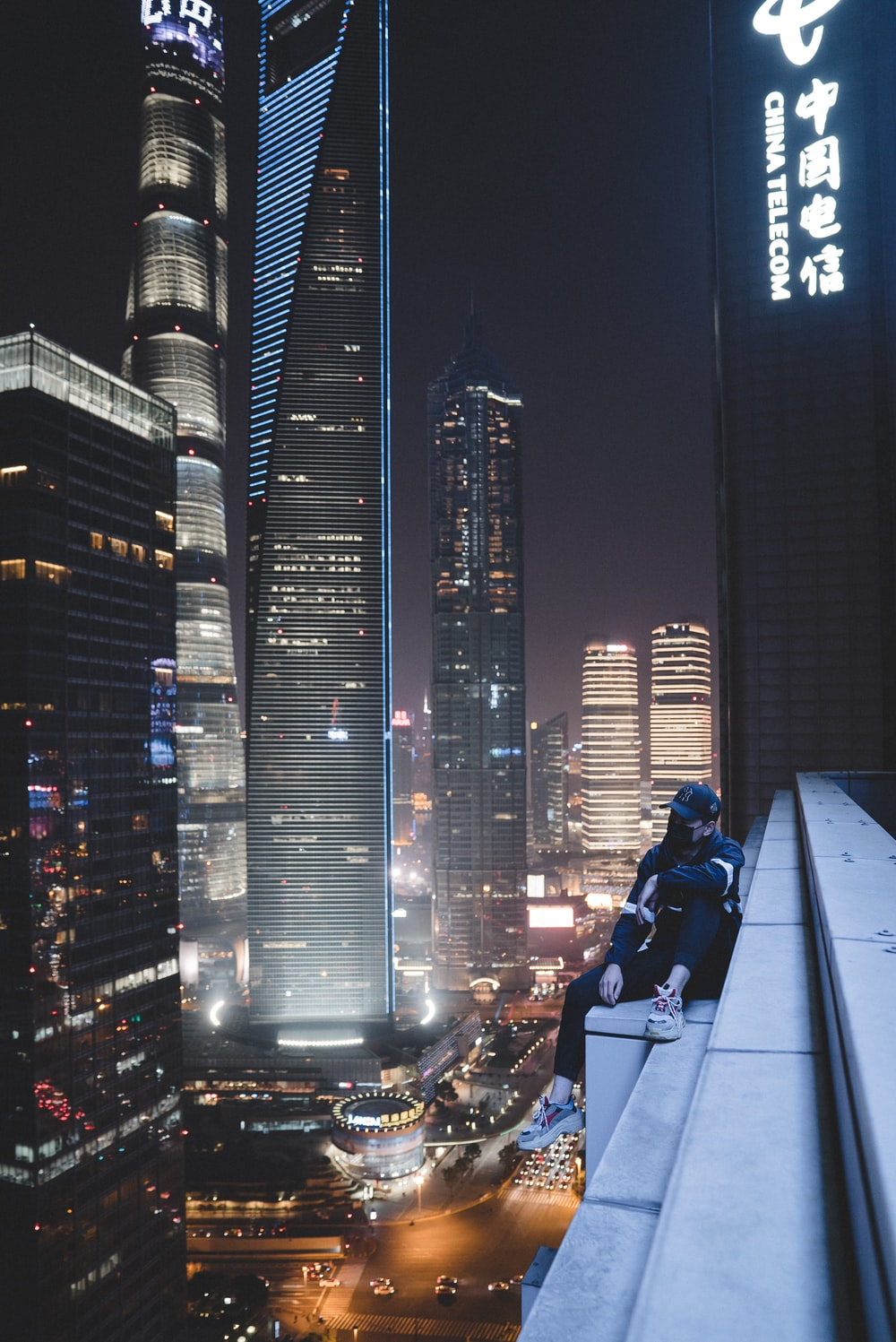man sitting on building gutter during nighttime