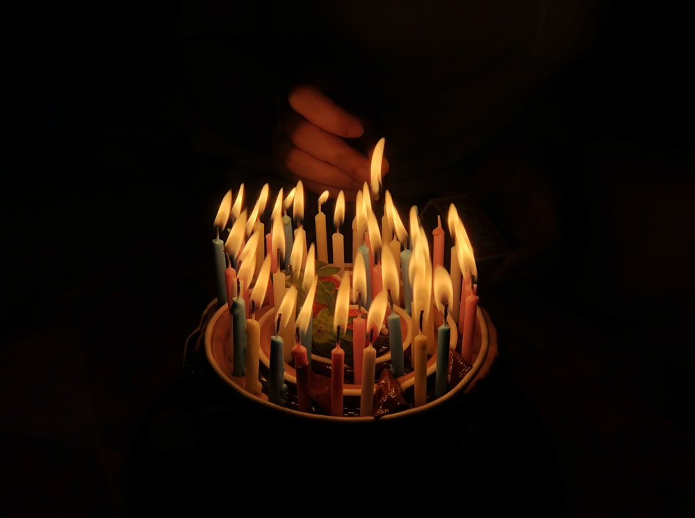 person touching assorted candles