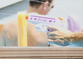 person holding pink and white Splash water gun