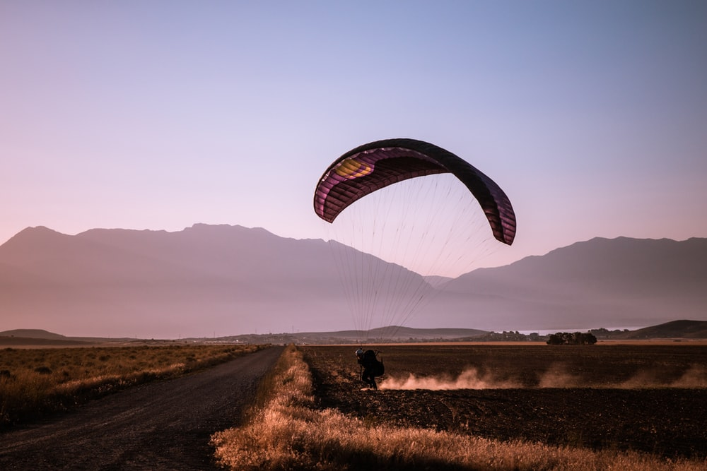person paragliding on field during daytime