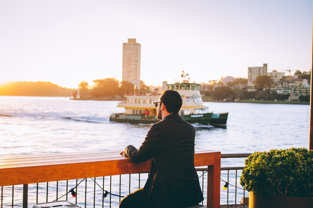man standing on bridge looking at the water