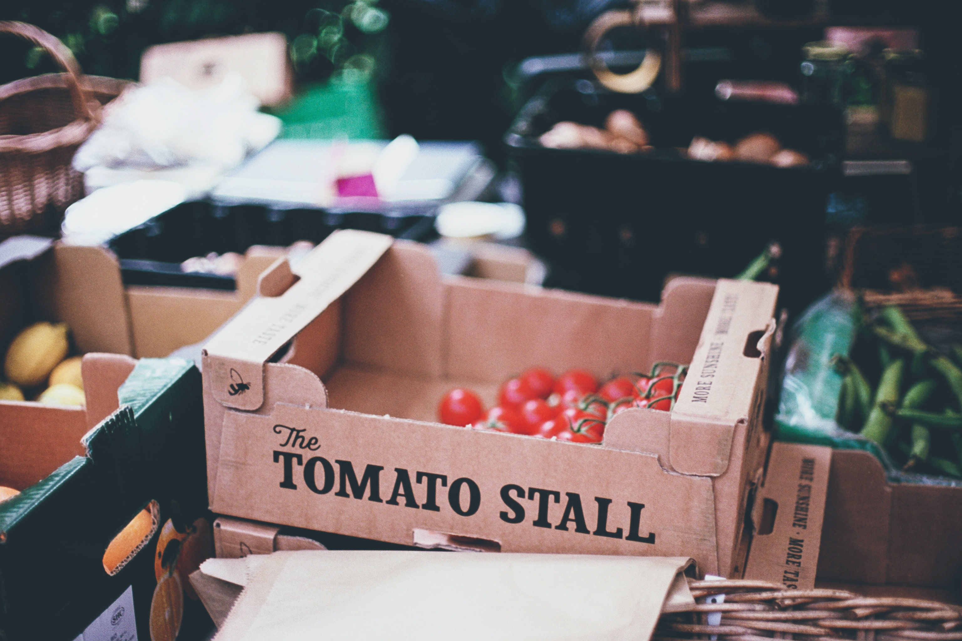 selective photography of tomato stall box on crate