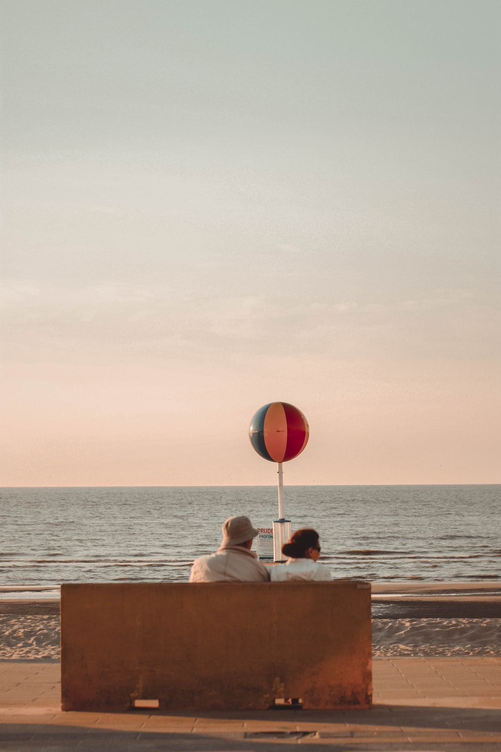 man and woman sitting in front of beach