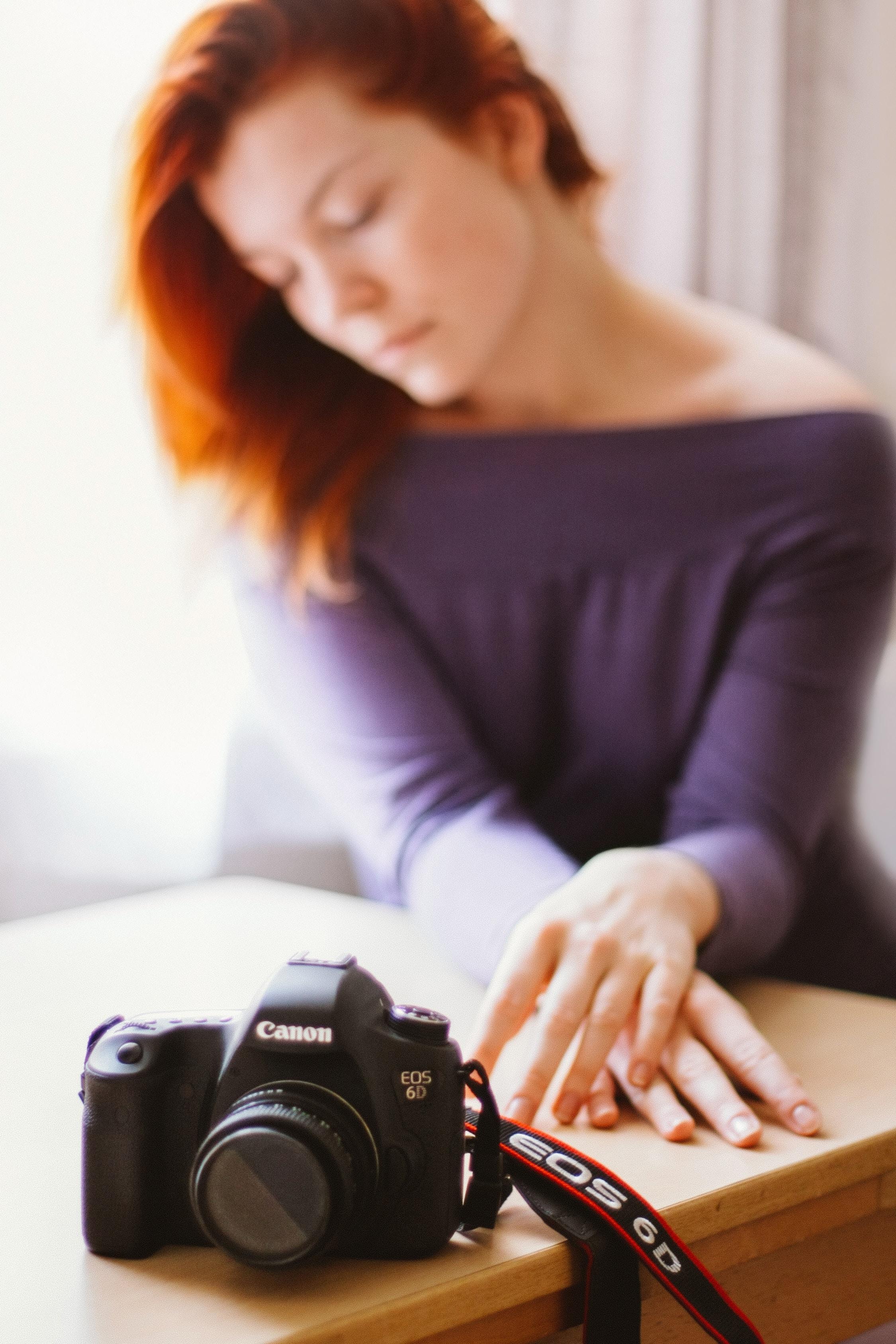 black Canon DSLR camera on table
