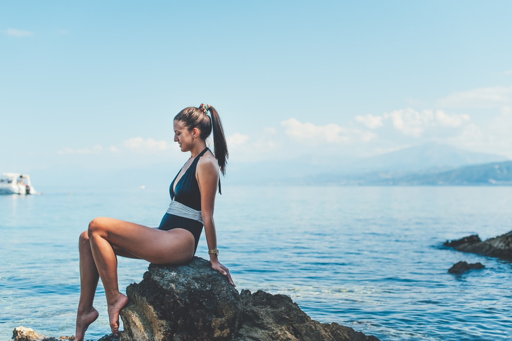 woman wearing monokini sitting on brown rock near shore