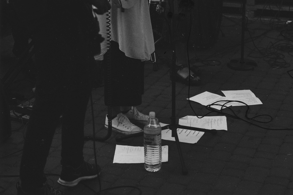 grayscale photo of three person's feet standing near microphone stands