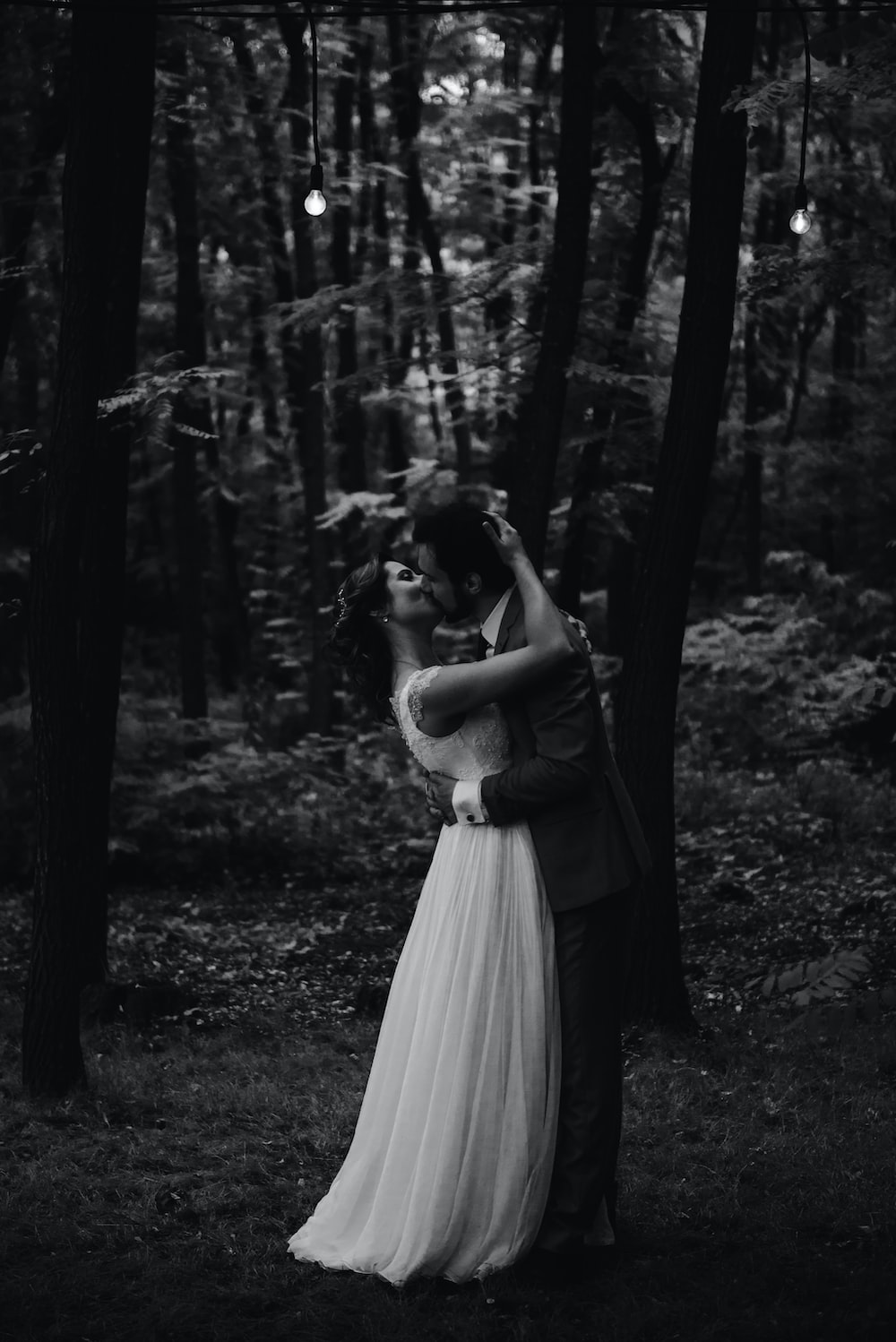 grayscale photo of couple kissing under forest trees