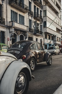 black Volkswagen beetle on roadway near white concrete buidling