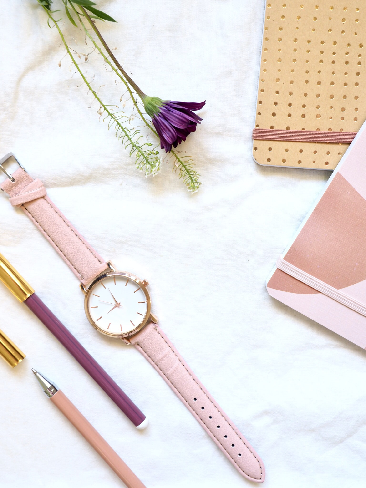 round gold-colored analog watch with pink leather band at 9:00