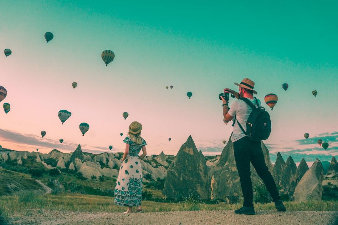 man taking photo of hot air balloons