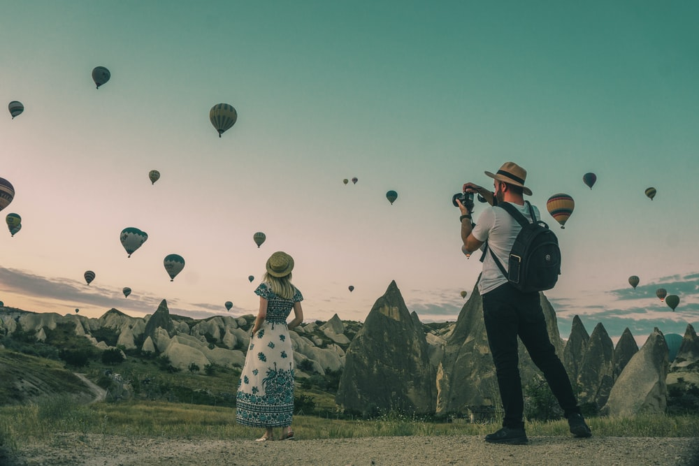 man taking photo of hot air balloons
