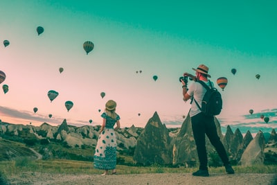 man taking photo of hot air balloons travel teams background