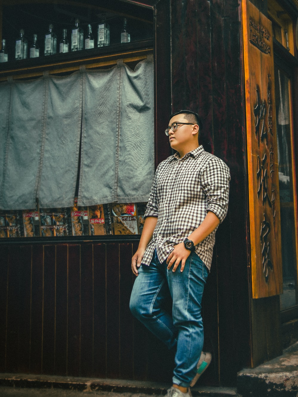 man in brown dress shirt leaning on wooden wall