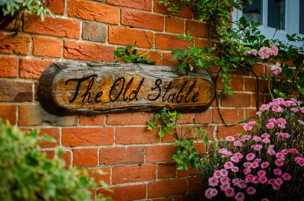 the old stable signage near pink flowers