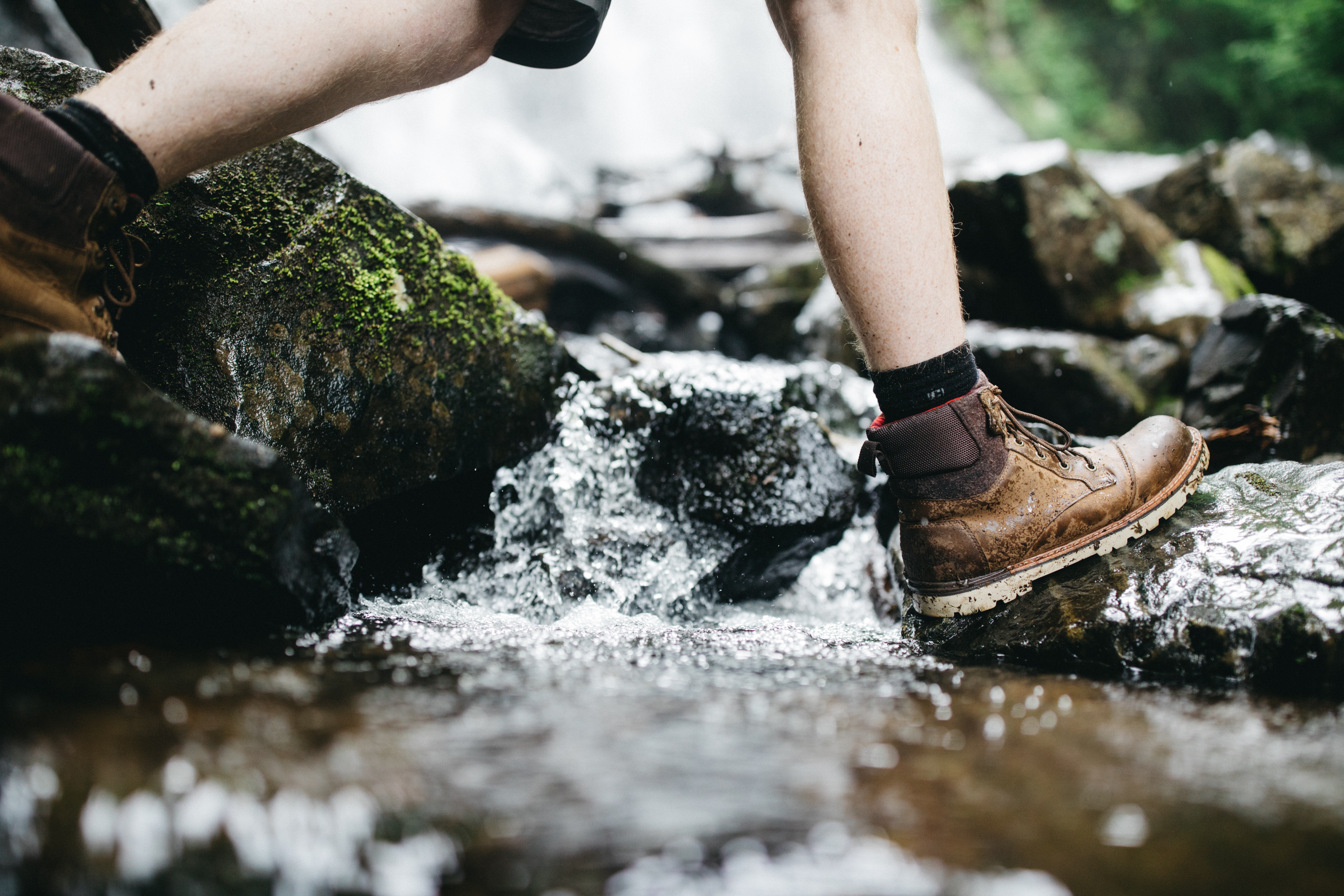 person stepping on rock