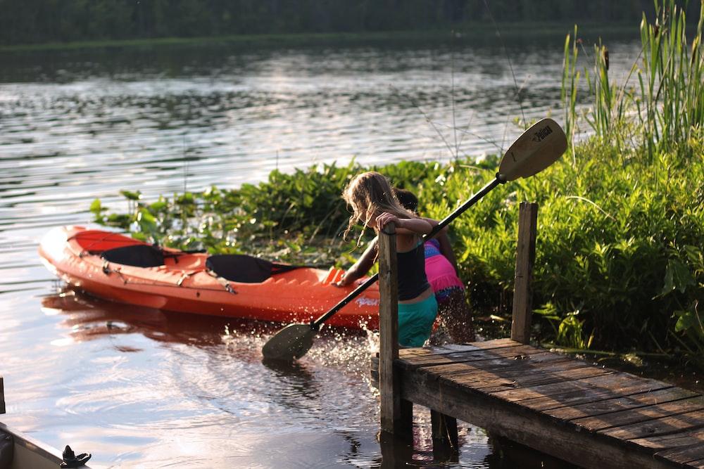 two girls near orange kayak in river