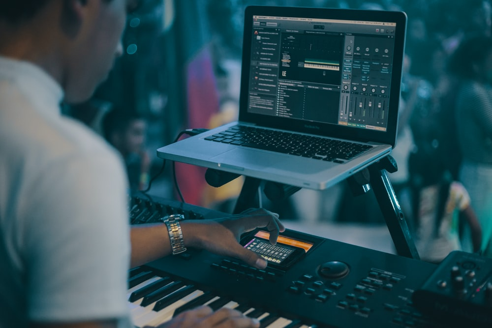person playing electronic keyboard while recording