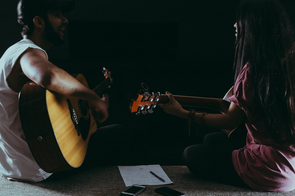 man and woman playing guitars