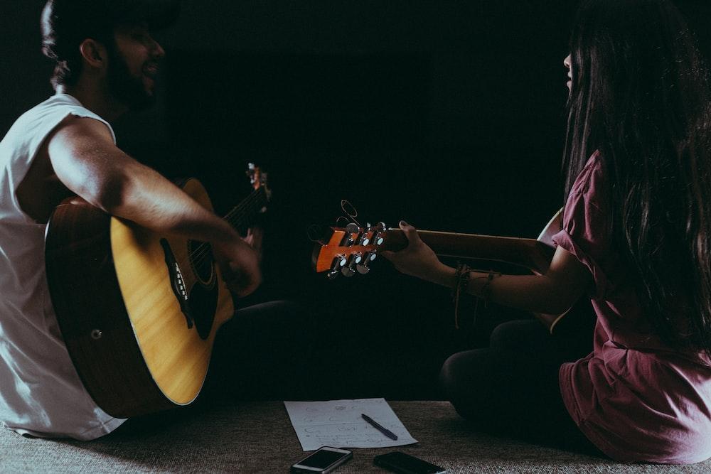 man and woman playing guitars