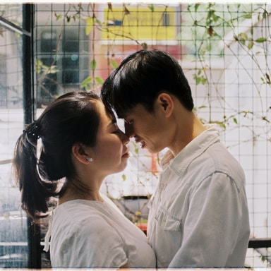 couple facing each other standing near fence