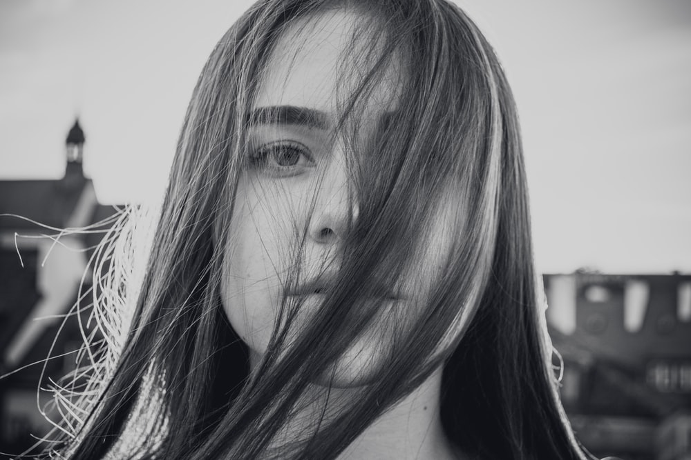 grayscale photo of woman covering her face on her own hair