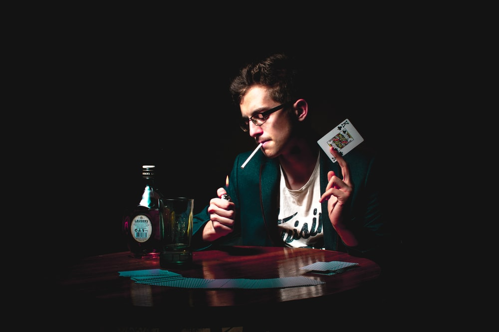 man lighting cigarette while holding playing card
