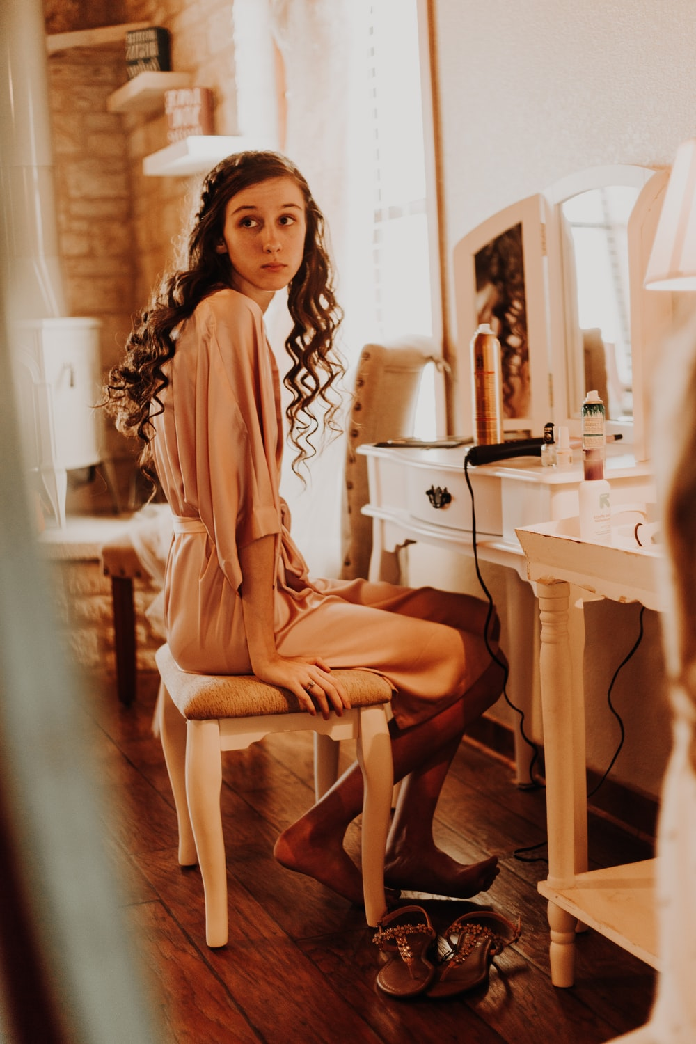 woman sitting in front of vanity table