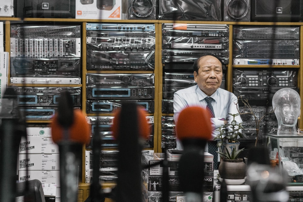 man beside stereo amplifiers