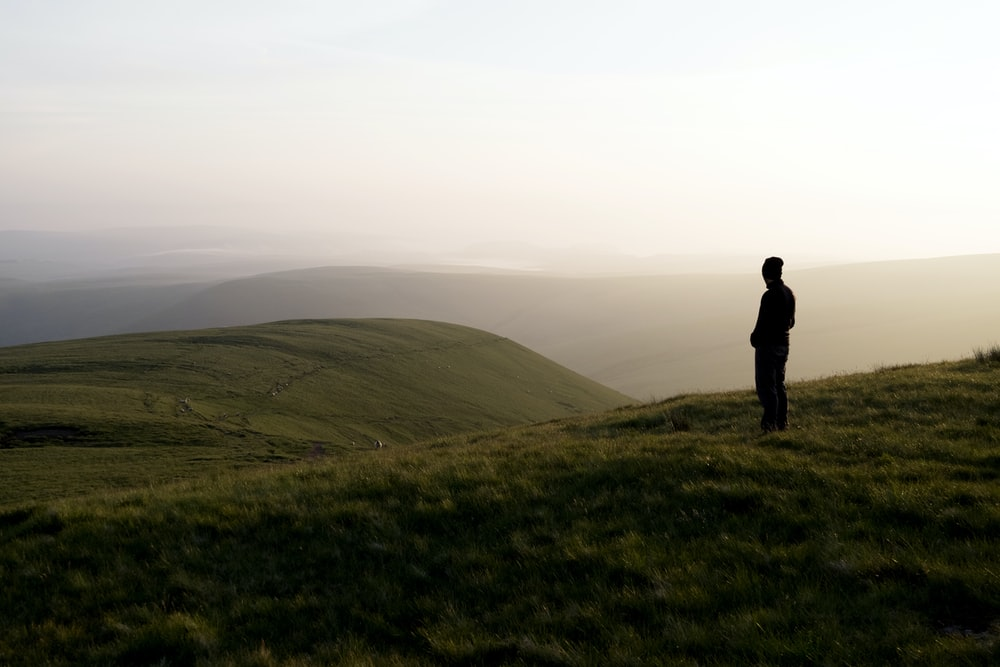 man standing on hill covered with grass