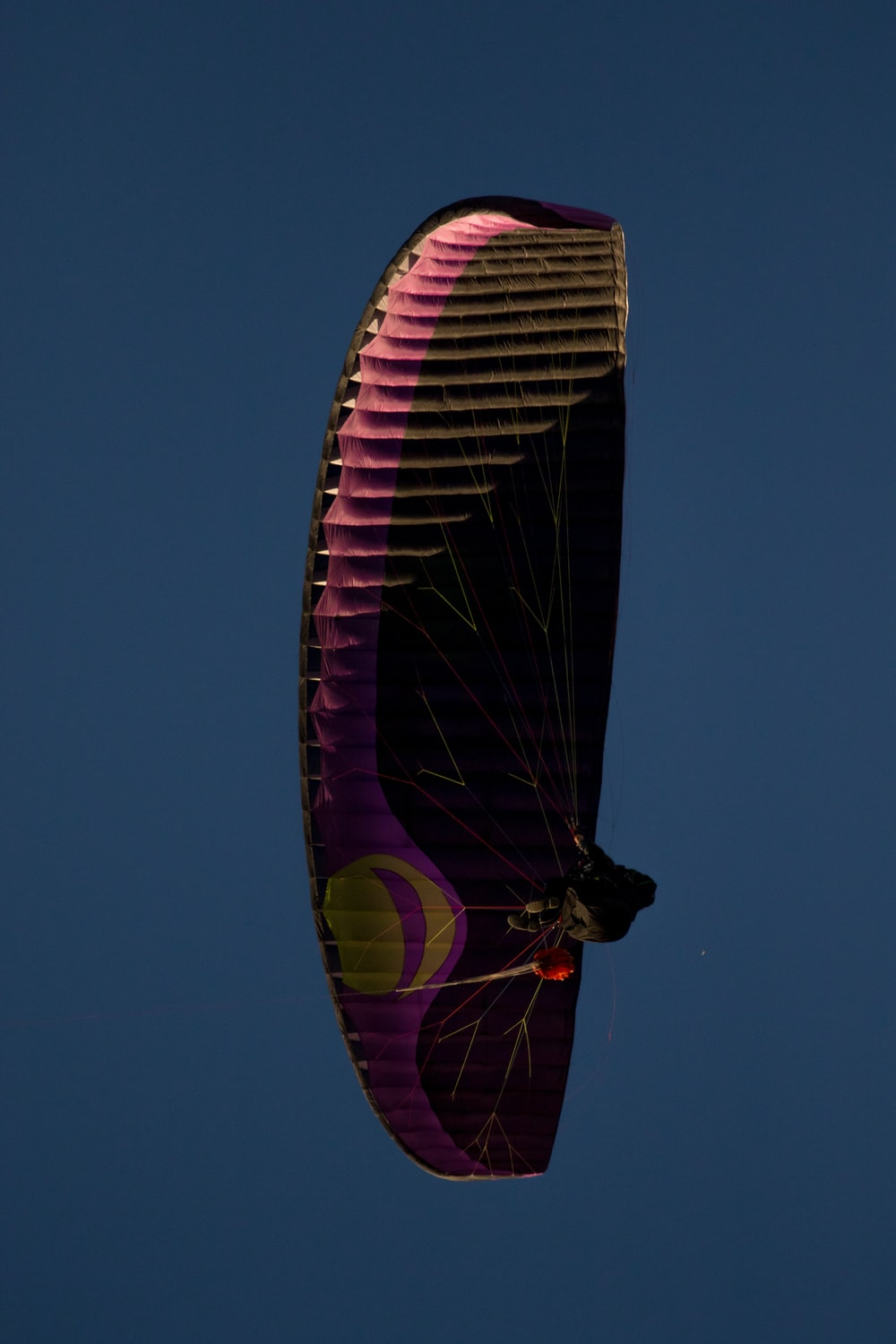 low-angle photography of person riding parachute in sky