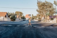 woman standing on pedestrian lane holding up flag of U.S.A.