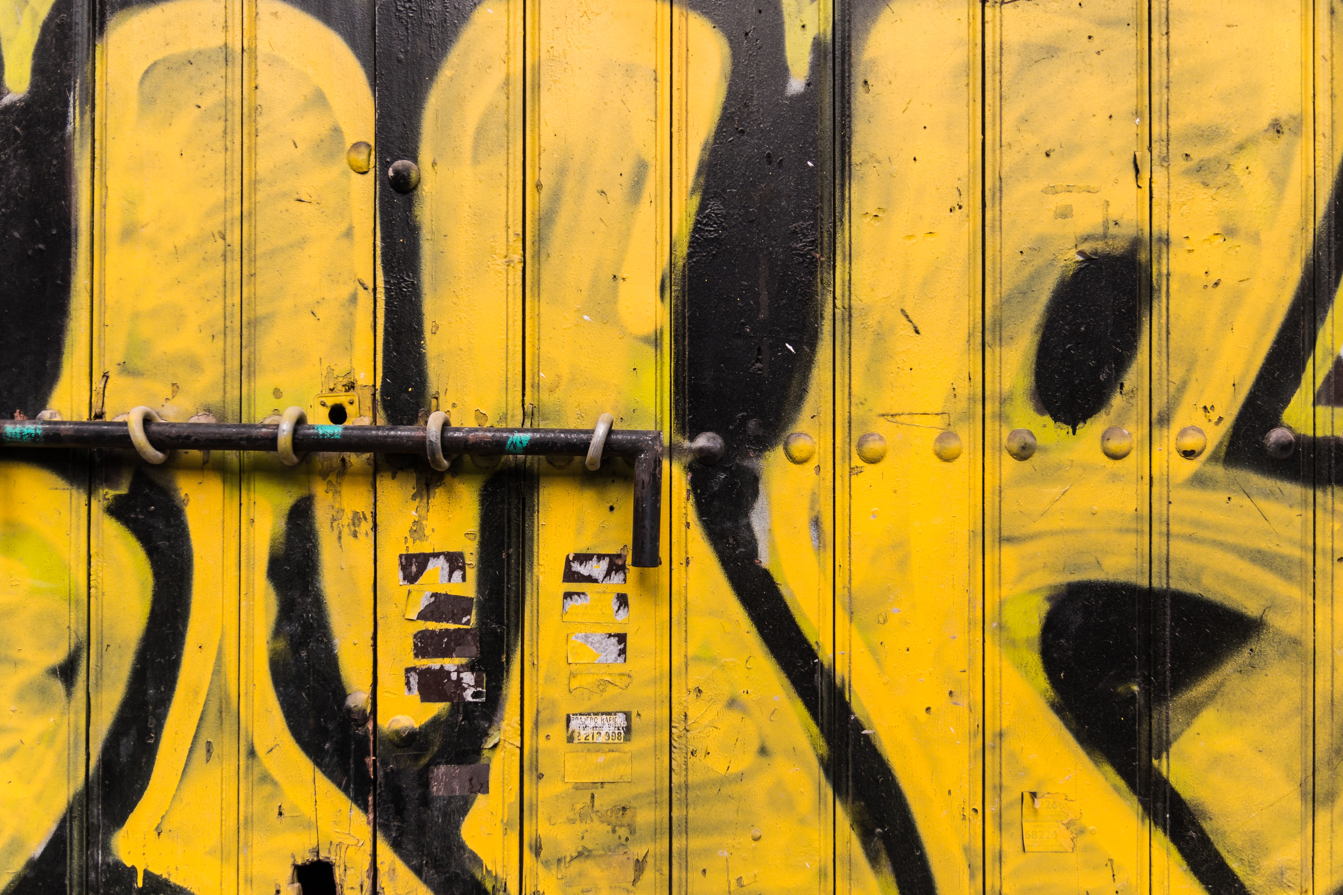 yellow and black wooden gate with graffiti and metal pole