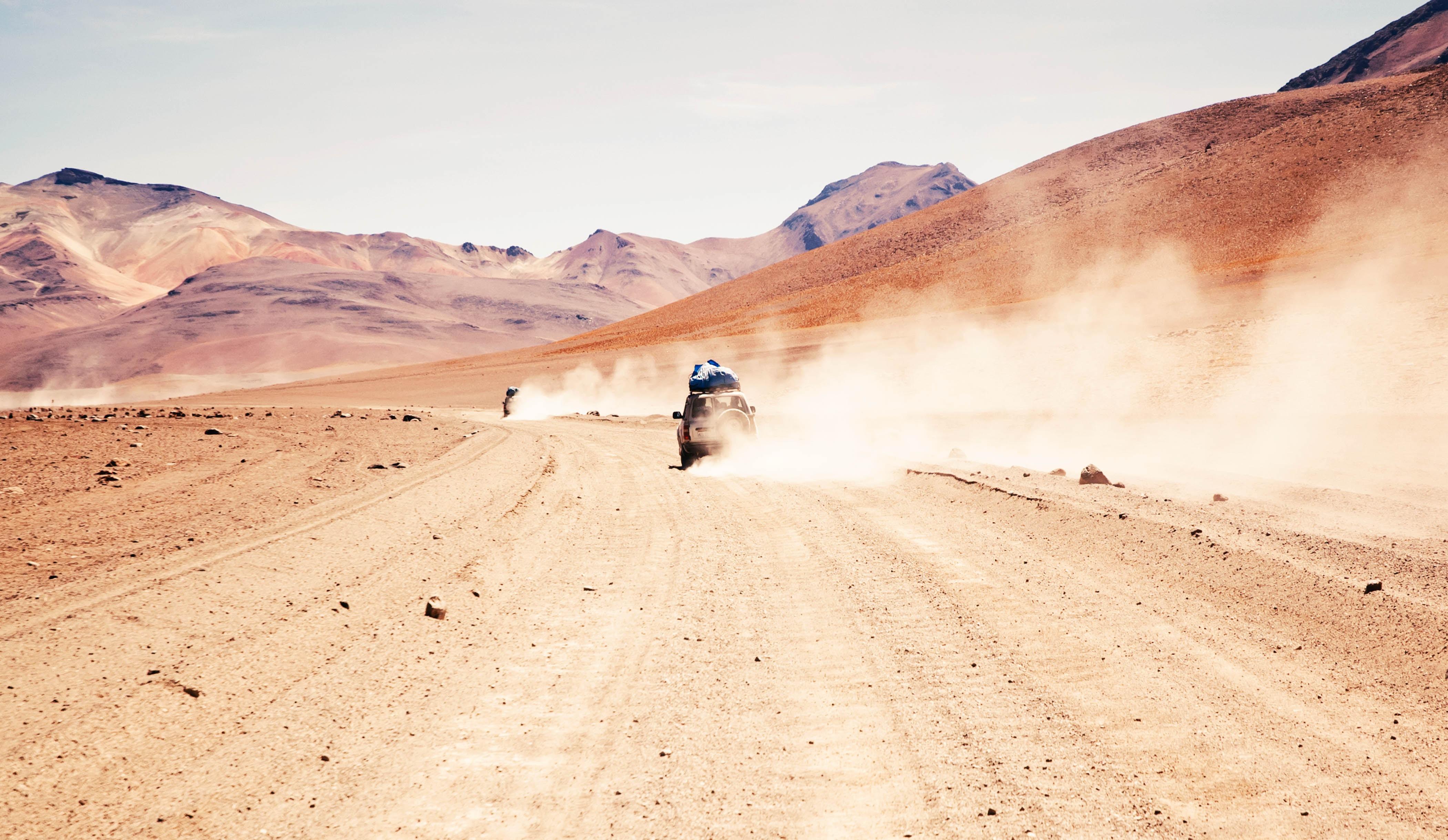 car traveling on brown soil