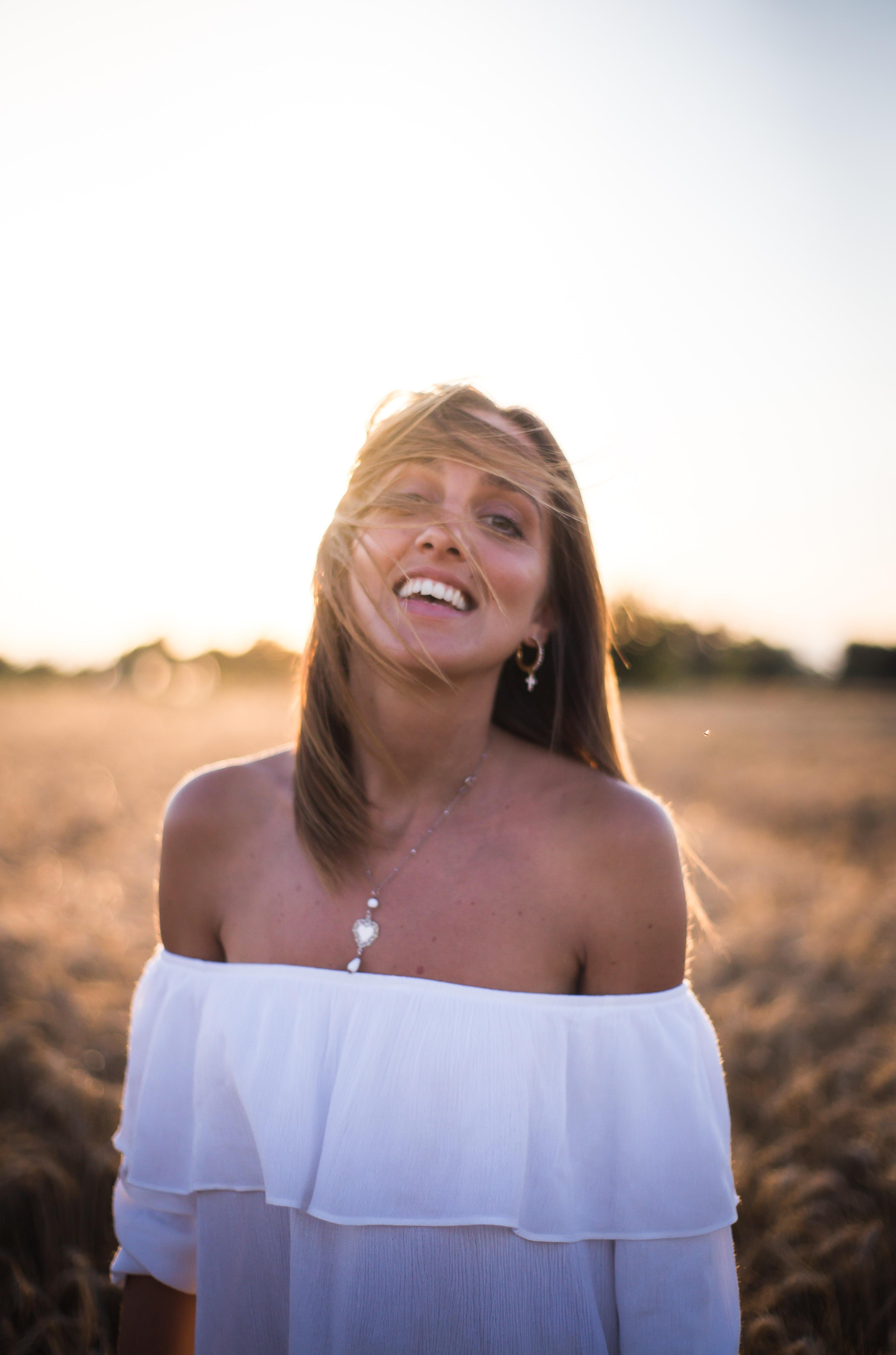 photo of smiling woman wearing white tube-top dress