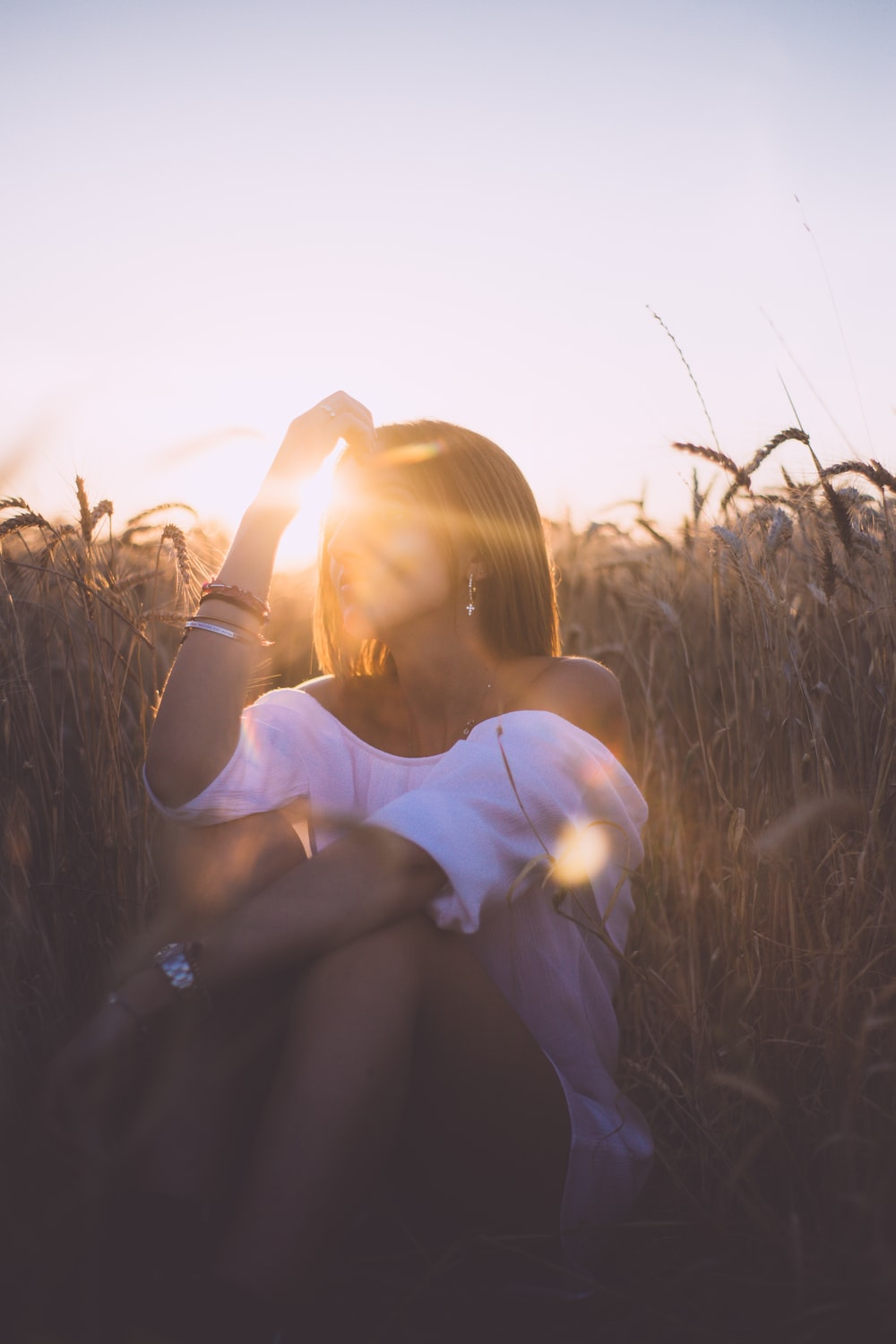 woman sitting on grass field during sunset