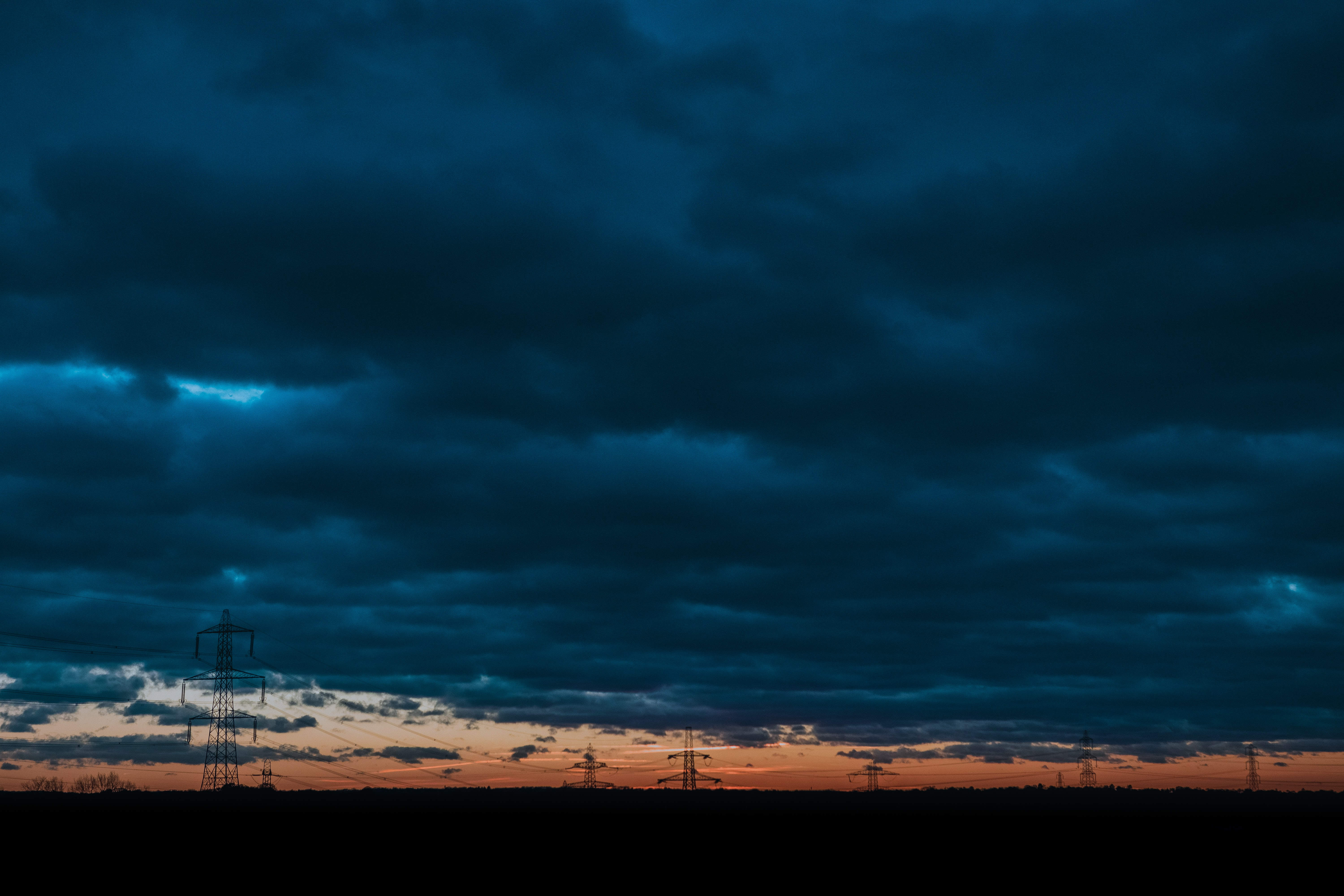 silhouette photo of transmission towers under cloudy skiy