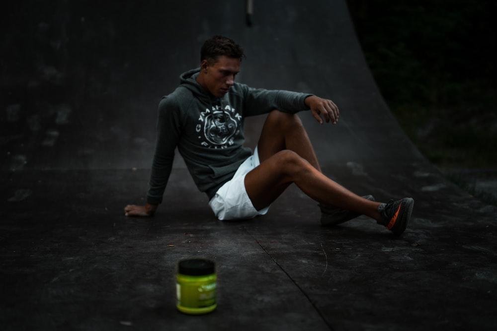 man sitting on skateboard tracks