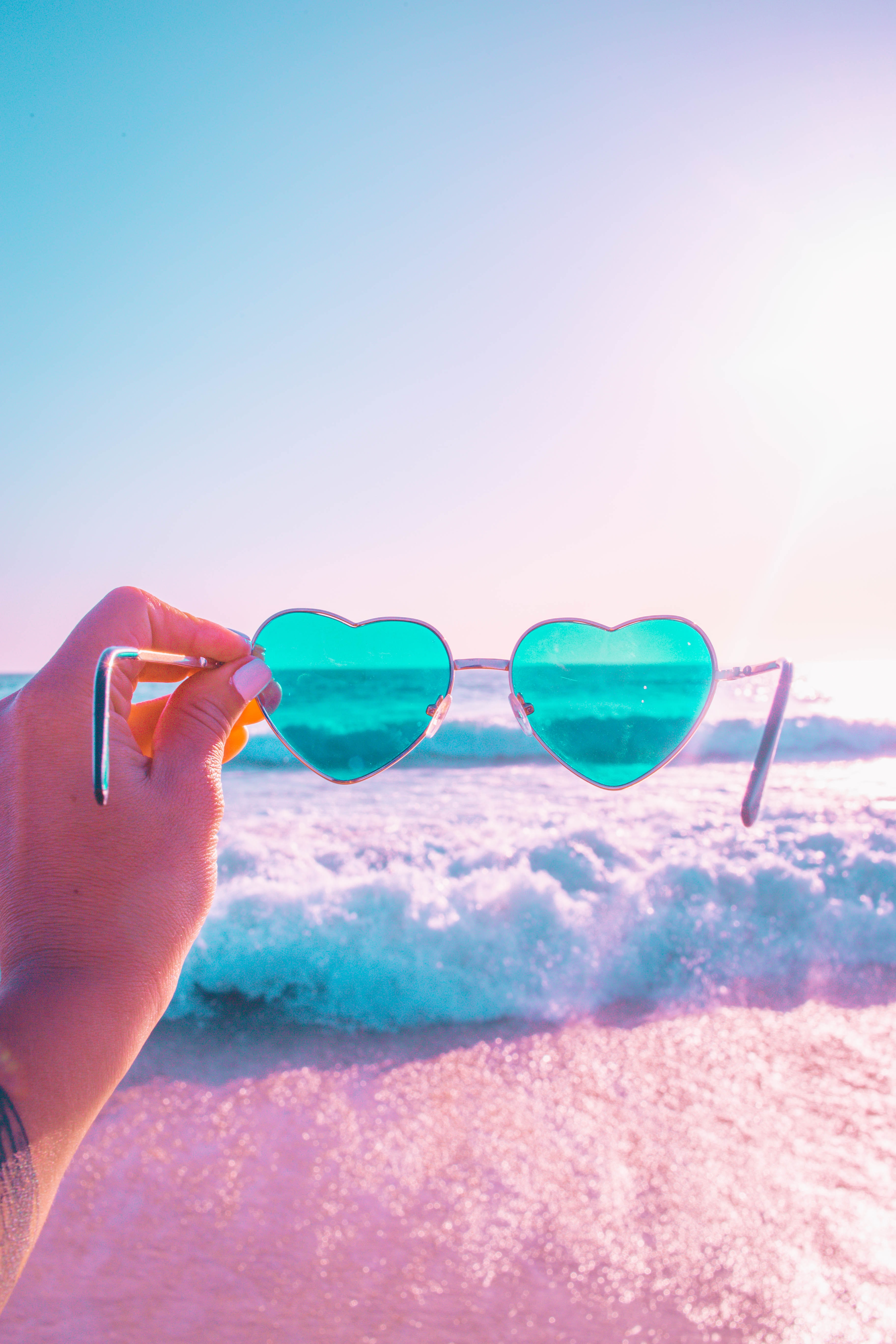person holding heart shaped teal sunglasses with silver frames