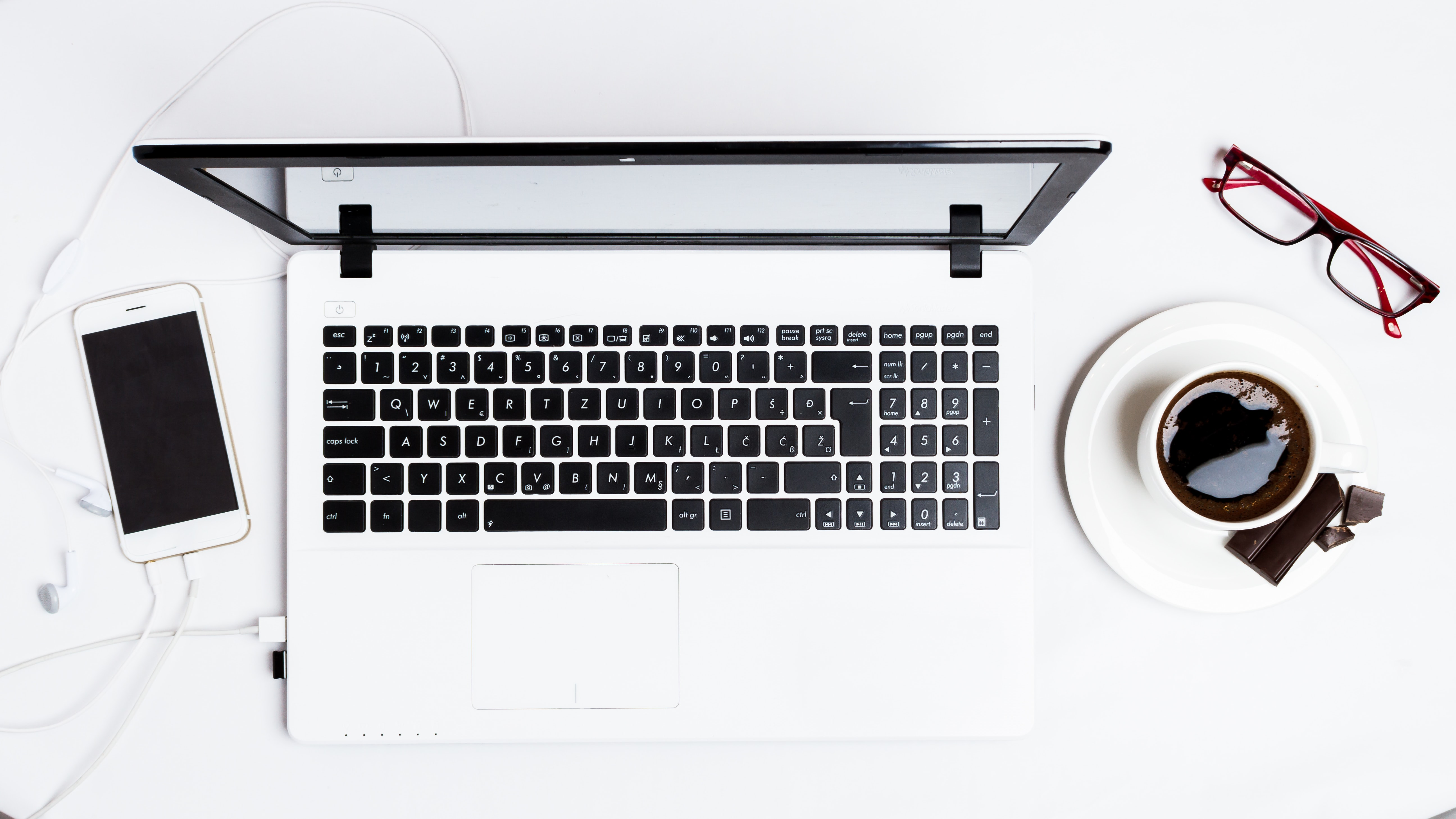 MacBook Pro between smartphone and teacup on white surface