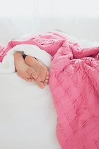 person lying on white mattress