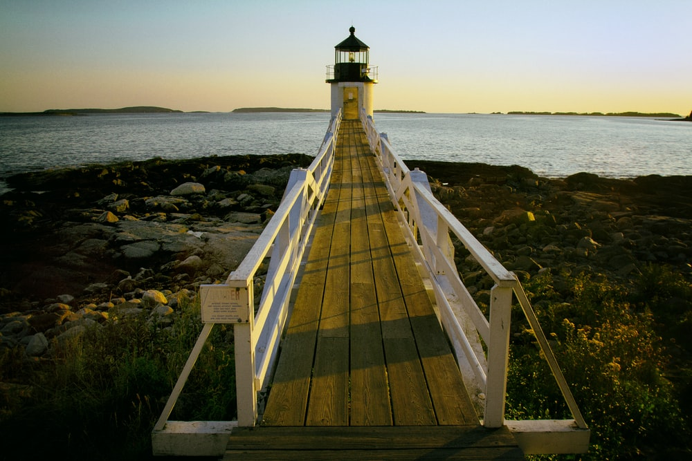 brown and white wooden dock with light house
