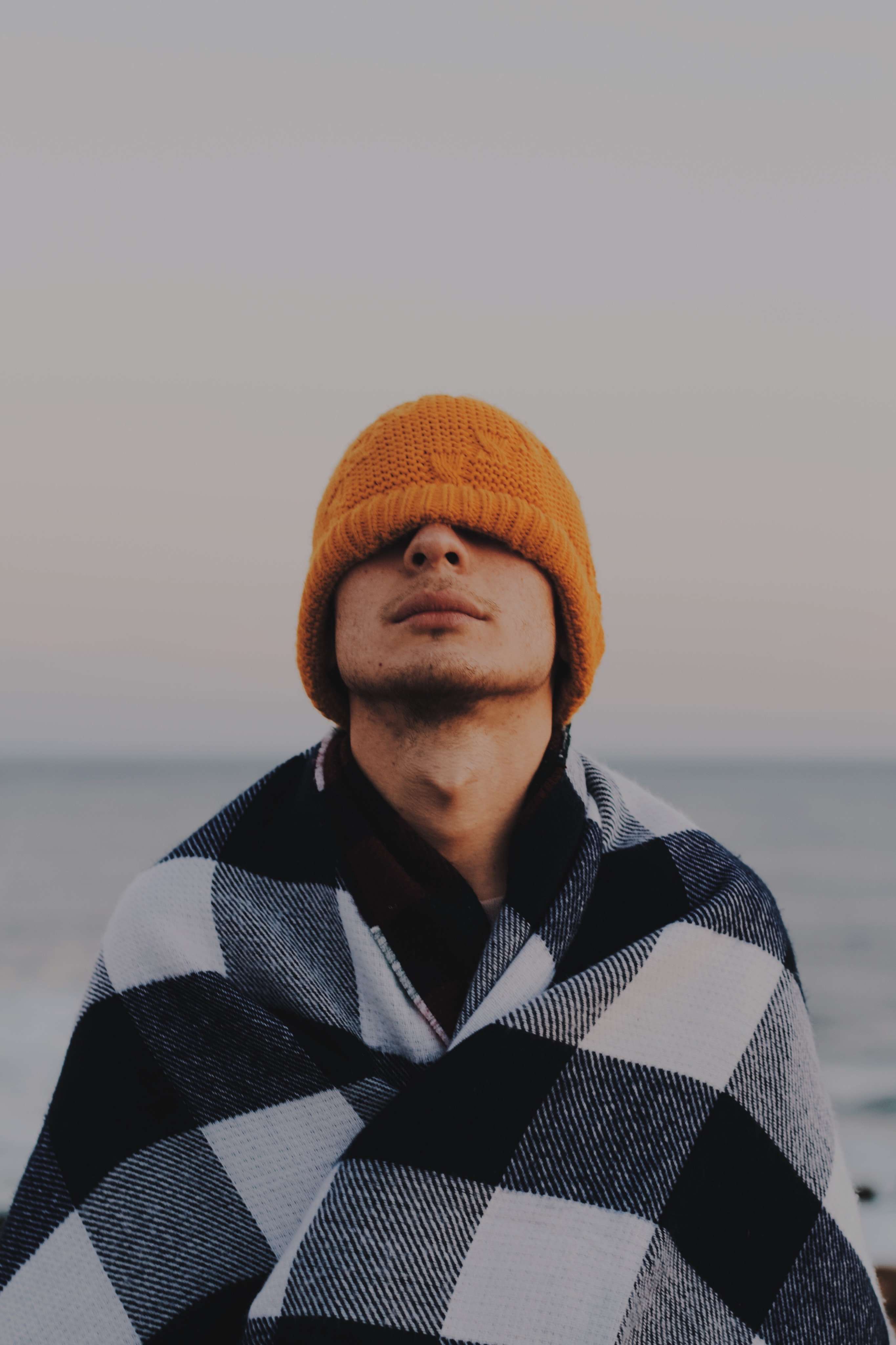 person covering his face by orange knit cap