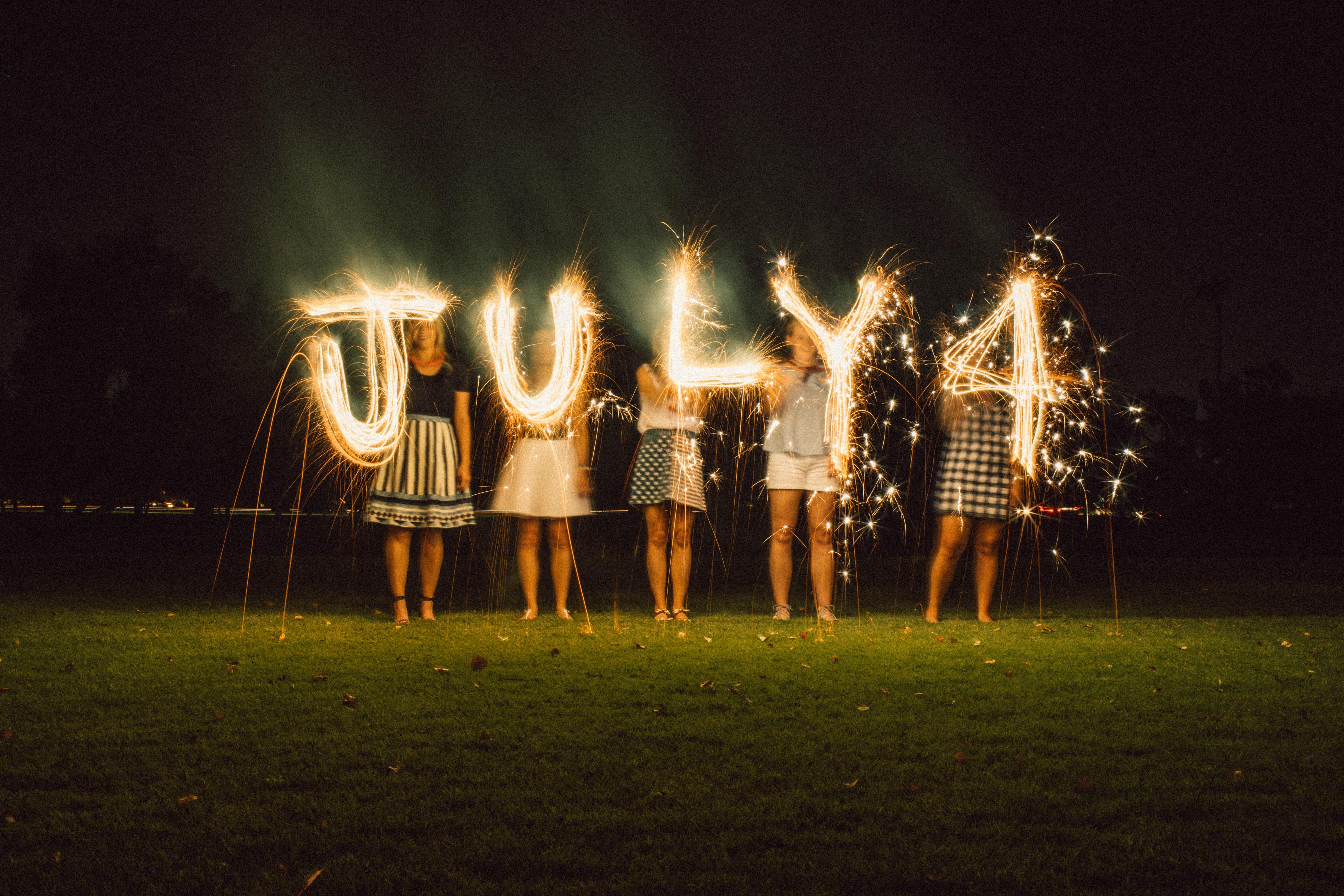 women holding July 4 string lights at night