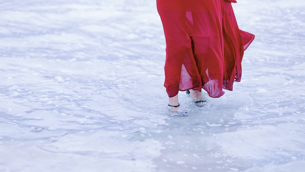 woman in red dress stepping on a body of water