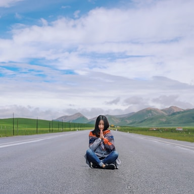 woman sitting on gray concrete road