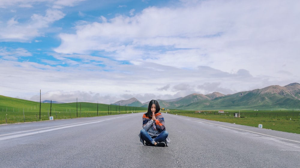 woman sitting on gray concrete road