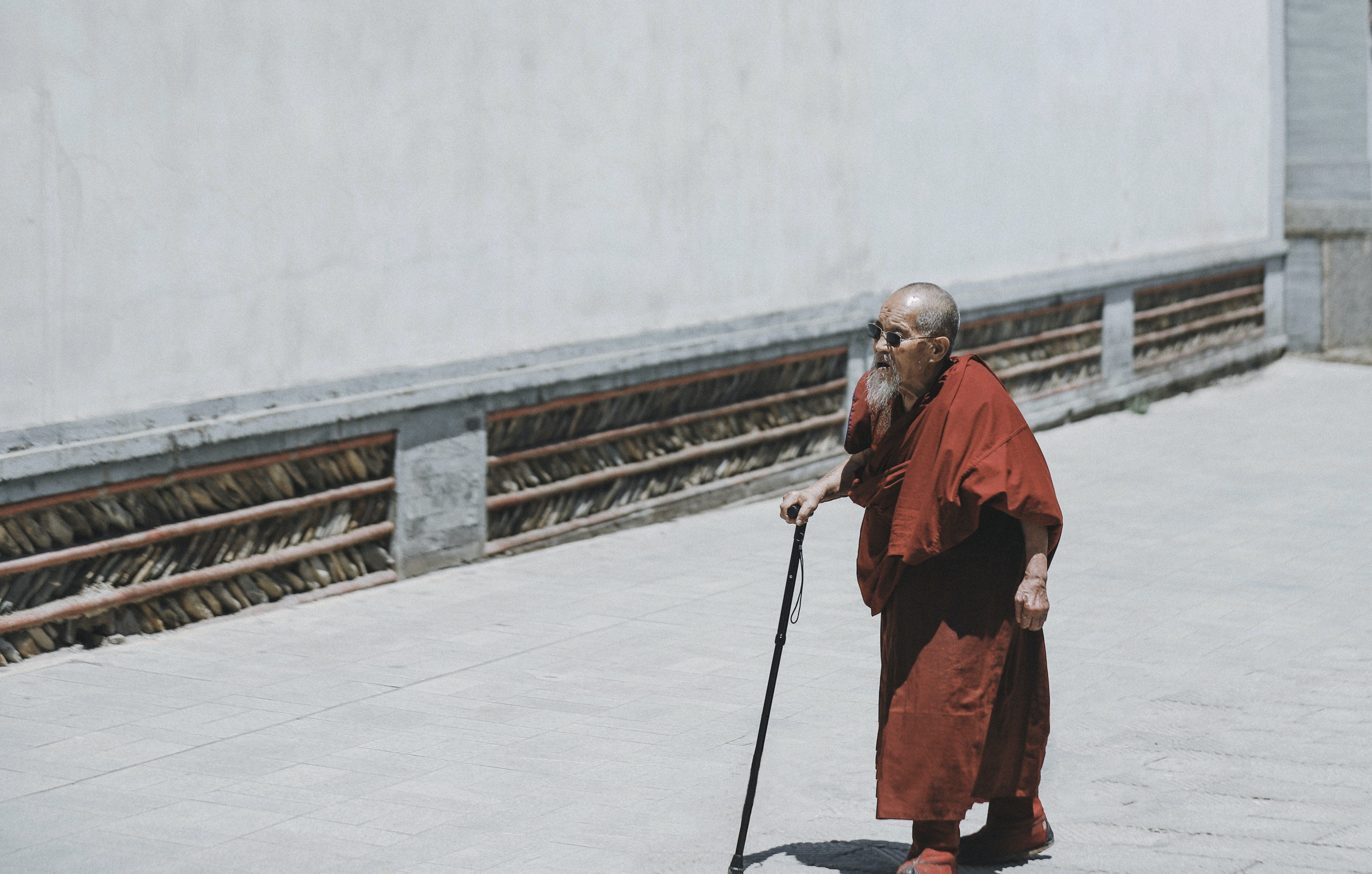 monk walking while holding cane near white wall