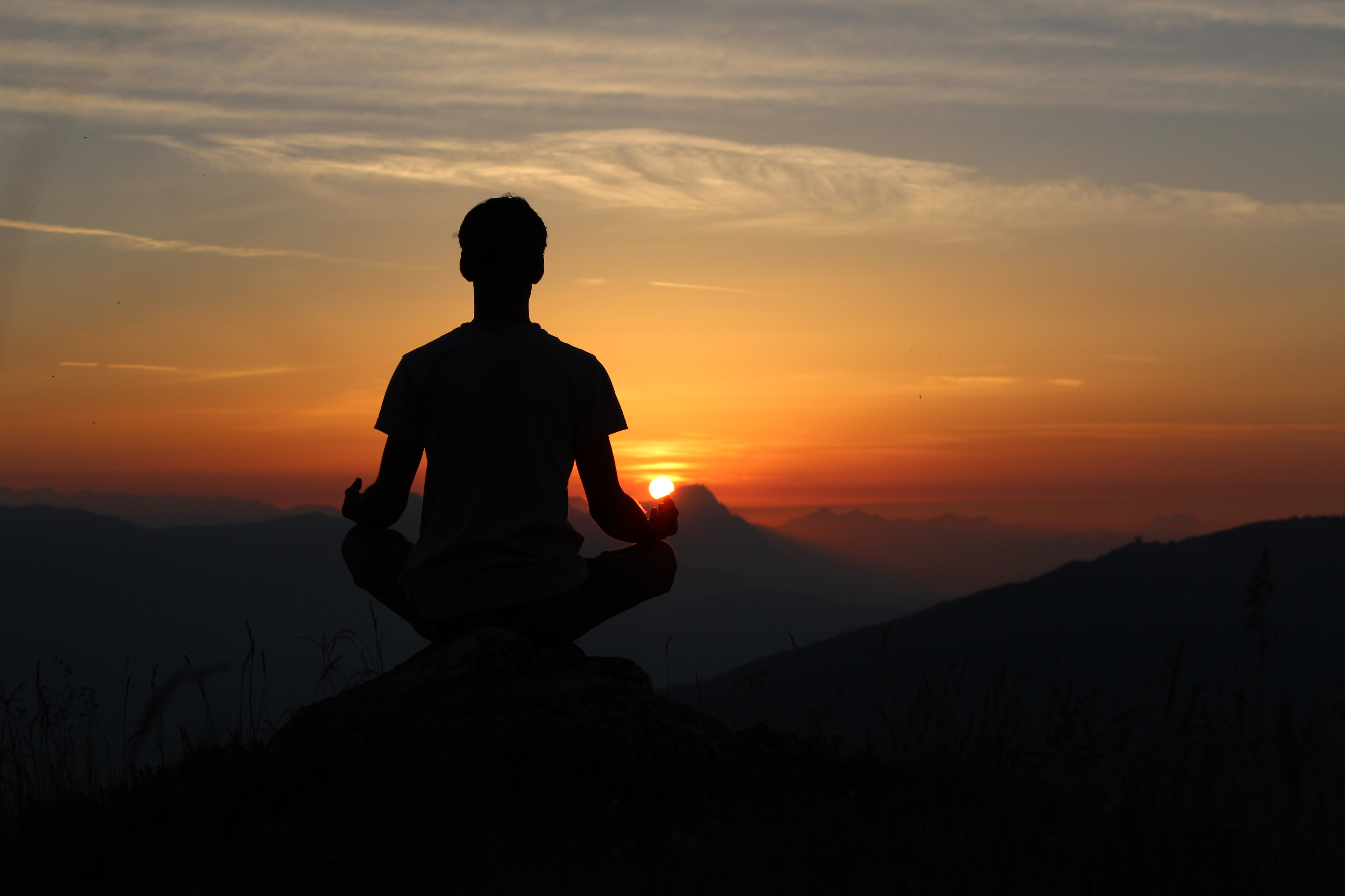silhouette of man meditating on rock cliff during golden hour